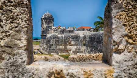 surrounding wall: A view of the wall and ocean in the distance as seen through one of the ramparts of the old city wall surrounding Cartagenas colonial city. Stock Photo