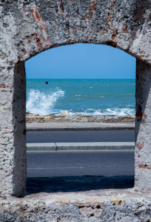 ramparts: The Caribbean Ocean kicks up waves and a bird flies by as seen through the ramparts of the old city wall around Cartagena.