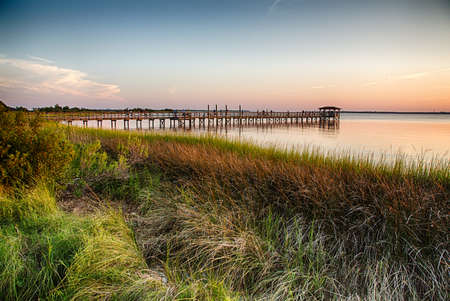 The pier on the Fort Fisher Recreation Area near Kure Beach, North Carolina with the sunsetting in the distance.