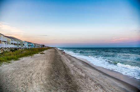 Fischer an der Küste von North Carolina, wie die Wellen am Strand zum Absturz bringen. Wilmington, NC. Standard-Bild