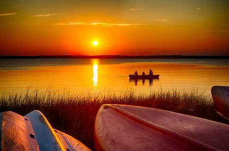August 14, 2015 Fort Fisher Air Force Recreation Center, Kure Beach, North Carolina, USA: A family views the sunset from a canoe on the Cape Fear River. 版權商用圖片