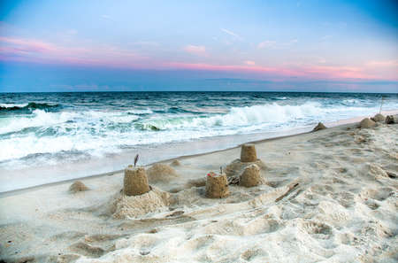 child's: A childs sand castle stands on the Atlandtic coast as the sun sets.