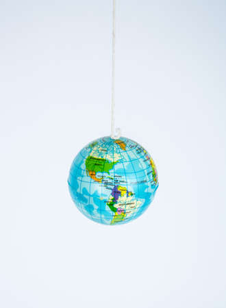 A small toy globe suspended on a string. Banco de Imagens