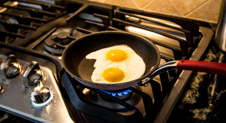 gas stove: Two eggs being fried in a non-stick skillet on a gas range.