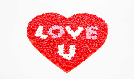 Red, WHite, and Pink candy hearts for Valentines day, arrainged in a large heart on a white background whit the phrase love u visible. Stock Photo