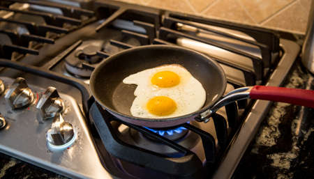 cooktop: Two eggs being fried in a non-stick skillet on a gas range.