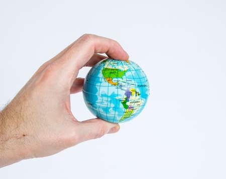 privilege: A white male hand holds a small globe. Symbolic of white privilege. Stock Photo