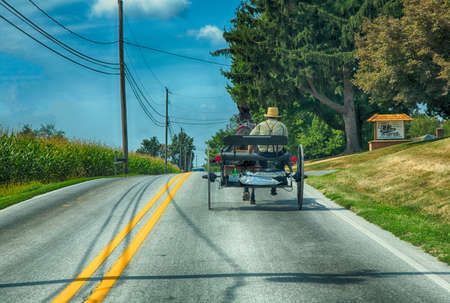 Lancaster, Pennsylvania - September 10, 2016 - An Amish man drives his buggy on a road in rural Pennsylvania.