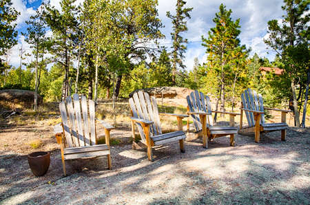 Adirondack chairs arainged on a rock overlooking a mountain and lake in the fall. Stock Photo