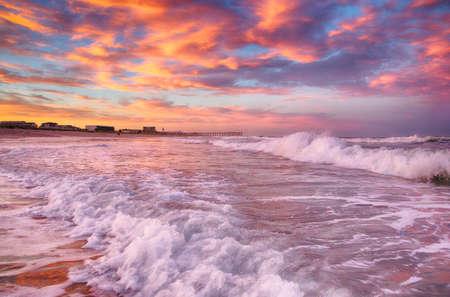 De zon gaat onder op de branding en het zand in Wrightsville Beach, NC.