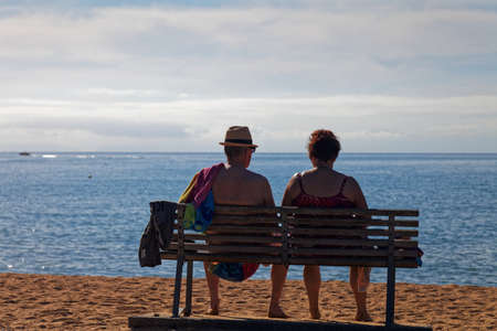 older couple enjoying sitting looking at the sea after a day on the beach Stock Photo