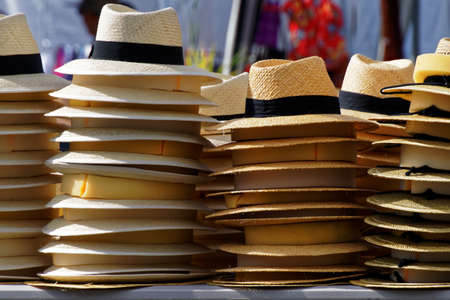 Stacks of straw hats on a market stall on a sunny day Stock Photo