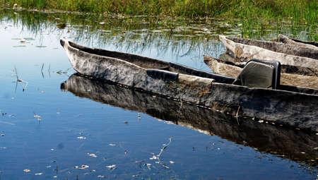 Closeup makoro dugout canoes reflected in still water, Okavango Delta, Botswana, Africa