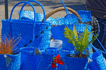 Blue shopping bags, shopping baskets, and flower pot holders made from upcycled packaging strap materials on a market stall Imagens