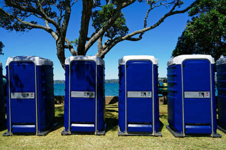 A row of outdoor four blue toilet cubicles at an event. Reklamní fotografie - 123103526