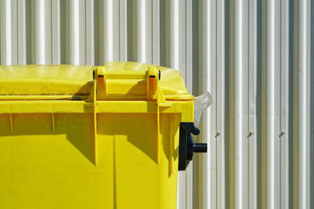 Bright yellow dumpster part view against a backdrop of a white industrial corrugated cladding or wall siding. Imagens
