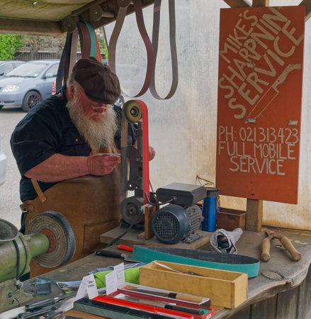 Matakana Farmers Market, MatakanaNew Zealand – November 4, 2017: A knife sharpener tradesman at work at the Matakana Farmers Market, Matakana, New Zealand.