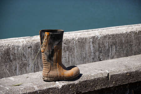 One lace up rubber boot, muddy and discarded at the sea front.
