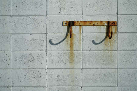 Rusty hooks on a rust stained breeze block wall at the sea front. Imagens