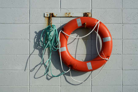 Red life saving ring attached to a tangled green rope hanging on rusty hooks on a breeze block wall. Imagens