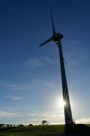 Brooklyn Wind Turbine against a clear blue sky with a sun starburst, Wellington, New Zealand. Imagens