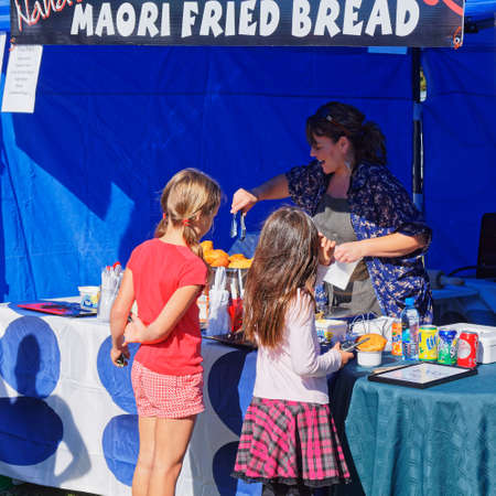 Mapua, TasmanNew Zealand – April 8, 2012: Maori fried bread being prepared for two young customers by a cheerful market stall holder. Editorial