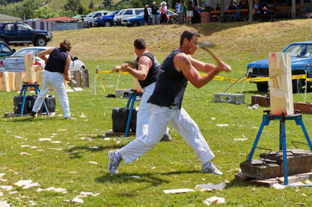 Tapawera, TasmanNew Zealand – January 14, 2012: Axemen in a wood chopping competition, Tapawera A & P (agricultural and pastoral) show.