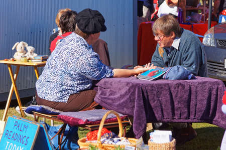 Mapua, TasmanNew Zealand – April 8, 2012: Palm reader at work at Mapua Easter fare.