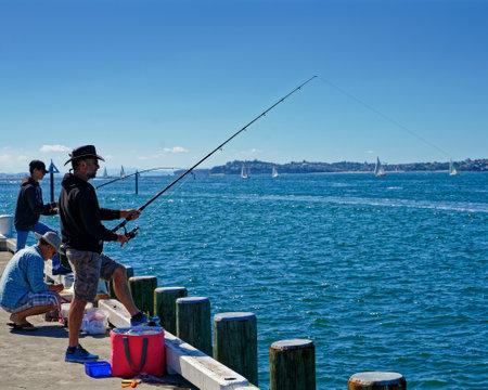 Devonport, AucklandNew Zealand - March 3, 2019: People fishing off the pier at Devonport, Auckland, New Zealand.