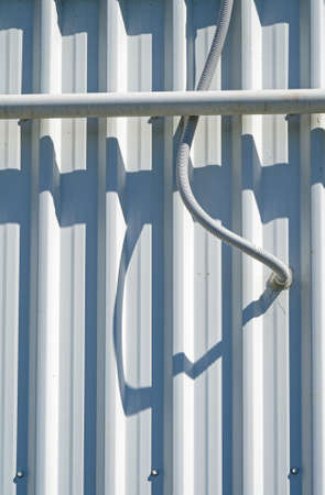 Twisted pipe sticking out of the corrugated steel siding of an industrial building.