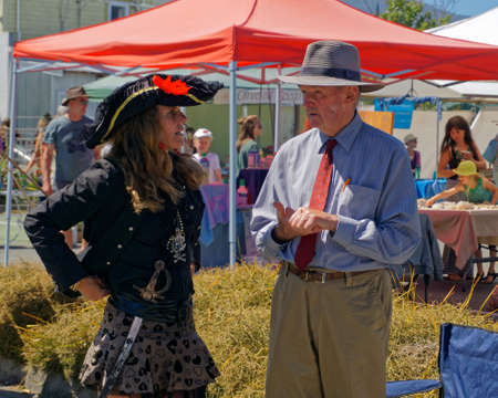 Takaka, Golden Baynew Zealand - January 29, 2017: Young woman dressed as a pirate talking to an older gentleman on the Jehovahs Witness market stall, Takaka market, Golden Bay, New Zealand. Editorial