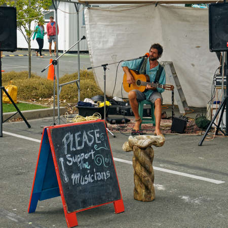 Takaka, Golden Baynew Zealand - March 14, 2015: Blackboard sign saying please support the musicians in front of a young man playing a guitar, Takaka market, Golden Bay, New Zealand.
