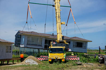 Motueka, Tasman/New Zealand - December 7, 2018: A house that has been sawn in two and moved to its new address being unloaded from a truck and placed in position.