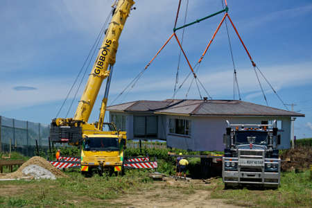 Motueka, TasmanNew Zealand - December 7, 2018: A house that has been sawn in two and moved to its new address being unloaded from a truck and placed in position.