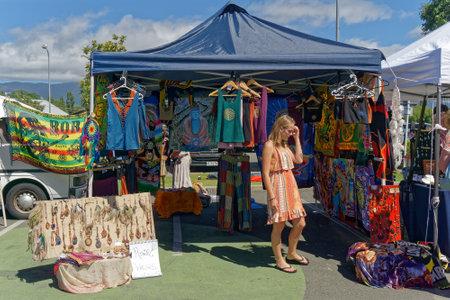 Takaka, Golden Baynew Zealand - January 29, 2017: Young woman clothes shopping at the Takaka village market, Tasman, New Zealand.