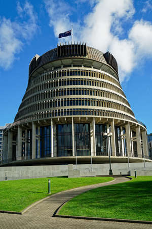 The Beehive - New Zealand parliament building with flag flying on a sunny day in Wellington.