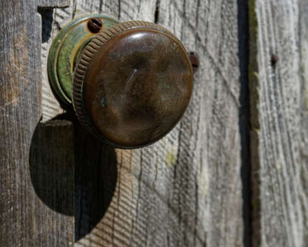 Worn and shiny metal door knob with green corrosion on an old shed. 写真素材
