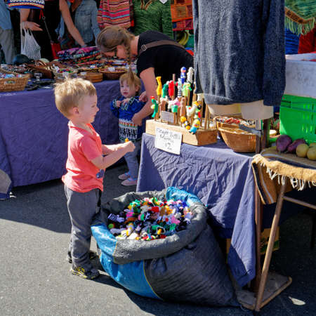 Nelson, NelsonNew Zealand - February 2, 2019: Small boy enthralled by the finger puppets on a Nelson market stall.