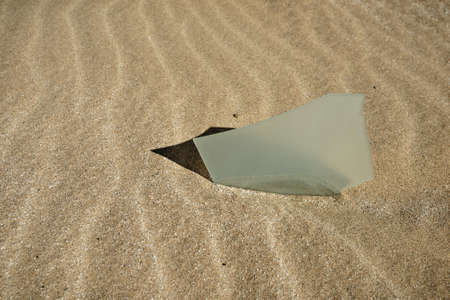 Cutting edge, jagged glass shard embedded in sand with shadow. Reklamní fotografie - 140622857