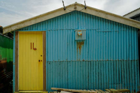 The number 14 in red on a rustic yellow shed door.