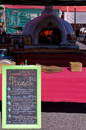 Motueka, Tasman/New Zealand - January 27, 2013: Motueka Sunday market stall making homemade pizzas. A blackboard menu. Editorial