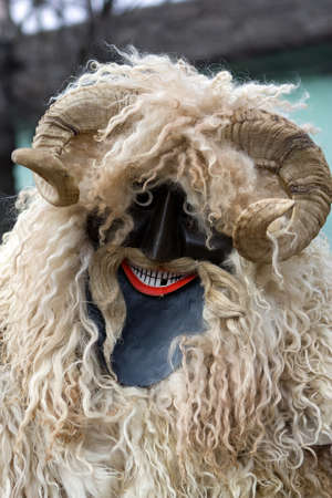 cs: Portrait of a buso in handmade, carved and painted mask and woolly outfit at the traditional Buso-walking