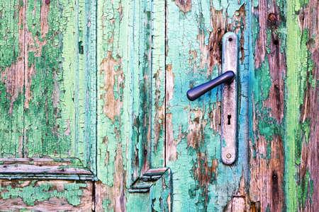 doorhandle: Doorhandle on old, green wooden door