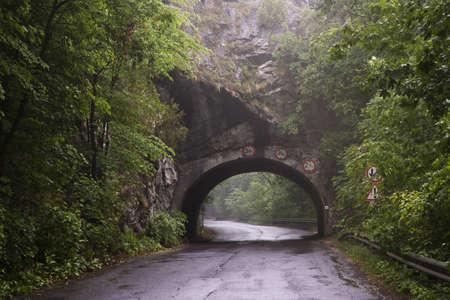 비포장 도로 Lillafured, Miskolc, 헝가리 근처 비오는 날에도 표지판과 산에서 터널과 숲 도로