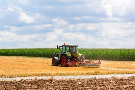 ploughing field: Agriculture - green tractor ploughing at the field on a sunny day.