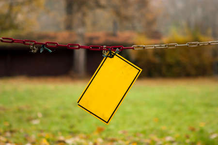 Empty, damaged yellow warning sign hanging on a dirty chain in the park - no text, lots of copy space.