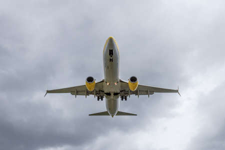 Overhead view of passenger airplane short before landing. Overcast, cloudy sky.