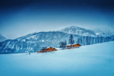 Romantic snowy winter landscape at early morning in the European Alps in Austria with snow, wooden buildings, blue sky and copy space. Stock Photo