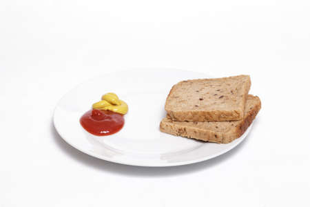 Ketchup, mustard and full grain bread slices on a white dish against white background. Helathy, vegan food concept.