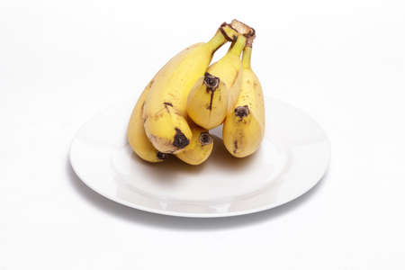 Bananas on a white dish against white background. Helathy, vegan food concept. 스톡 콘텐츠